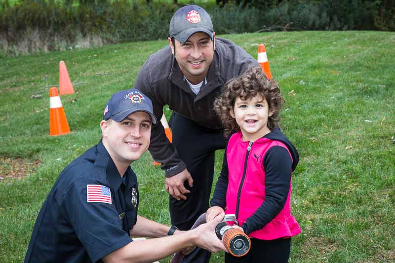 Members of the Long Grove Fire Protection District teach a young recruit how to handle the fire hose.