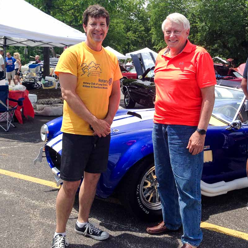 Lake County Board Representative Craig Taylor (on the right) shows off his vintage car to Aaron Underwood.
