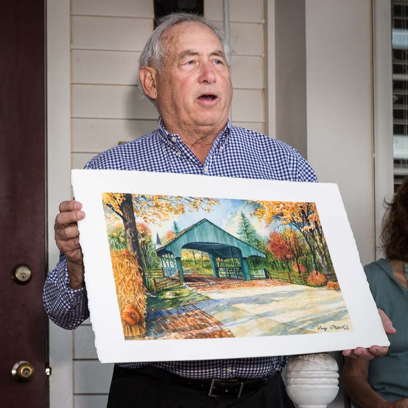 Long Grove Living magazine editor Harvey Stein shows off the watercolor painting that you can win in the raffle to benefit the Covered Bridge Fund.