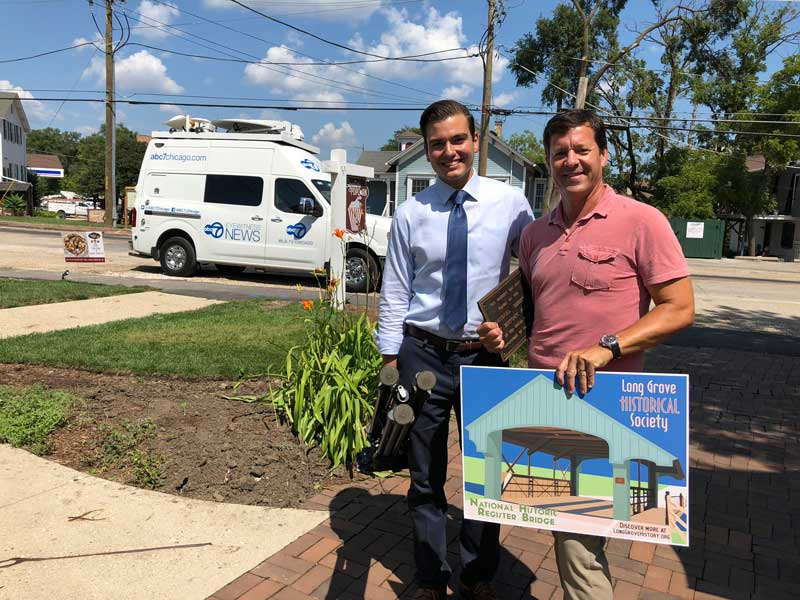 News reporter Mark Rivera stands next to Aaron Underwood (holding the bridge poster) after spending the morning in Long Grove on August 22nd.
