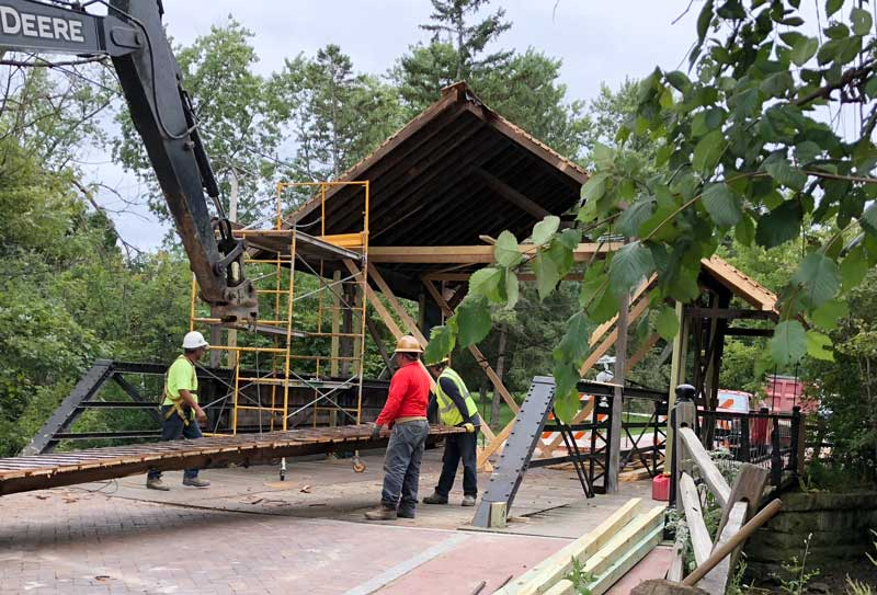 With the bridge covering two-thirds removed, the historic iron truss and walkway begin to emerge and become more visible.