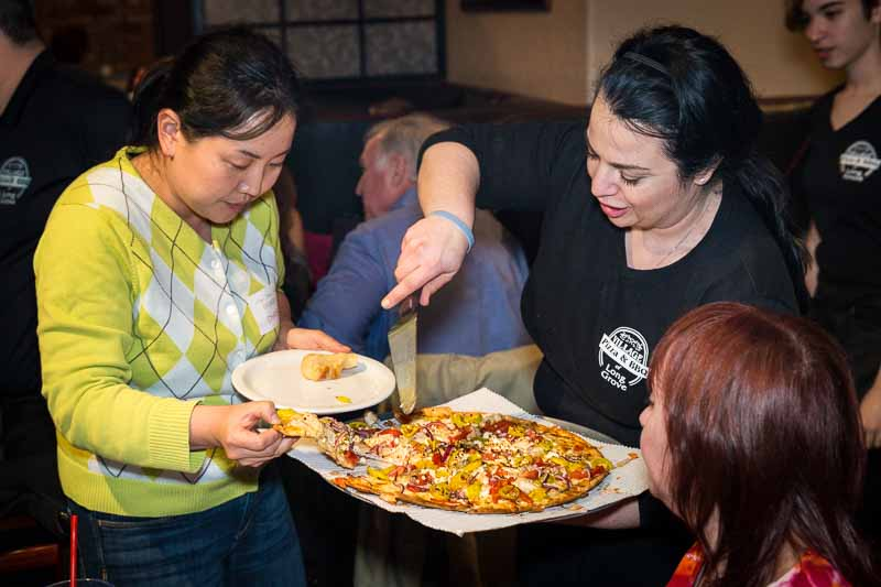 Joanie serves up a slice for an eager resident at a gathering Tuesday evening.