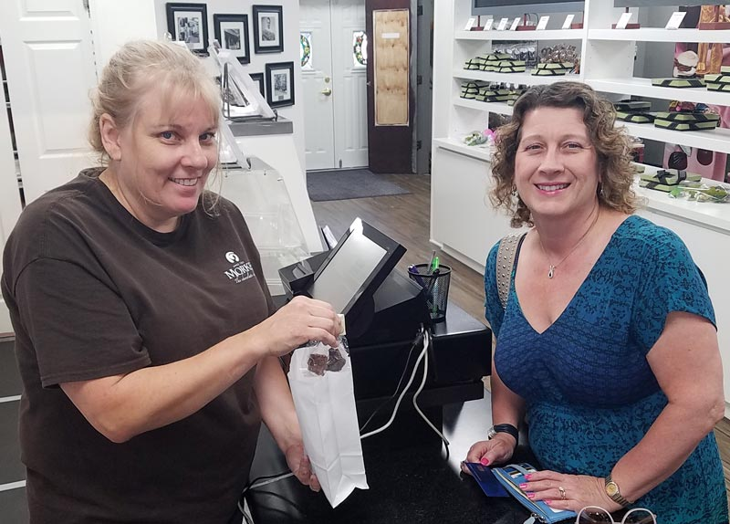 Cathie Olson is shown helping me satisfy another chocolate craving at the new Morkes Chocolates shop  in Long Grove.