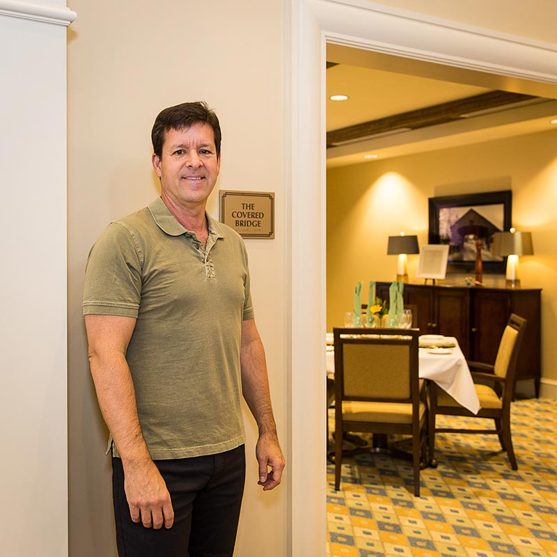 """Aaron Underwood stands next to the """"Covered Bridge Room"""" at Harbor Chase. The """"Crackerjack"""" lounge/bar area also pays homage to local history--it's the name of Long Grove's 1906 baseball team."""
